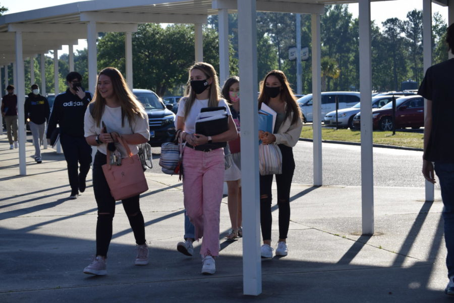 Students walk together in a group towards the school.