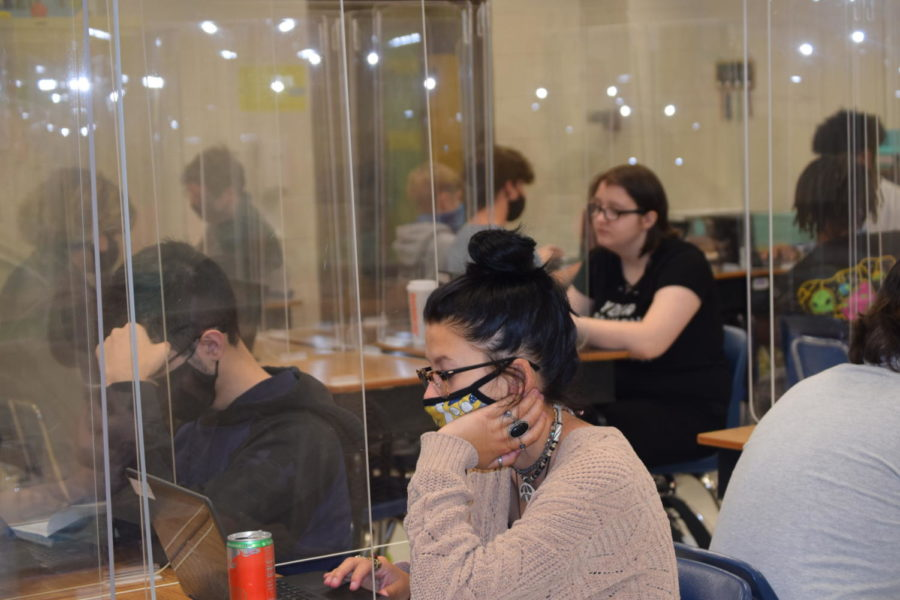 Sophomore Summer Wicker sits in her plexiglass next to a classmate