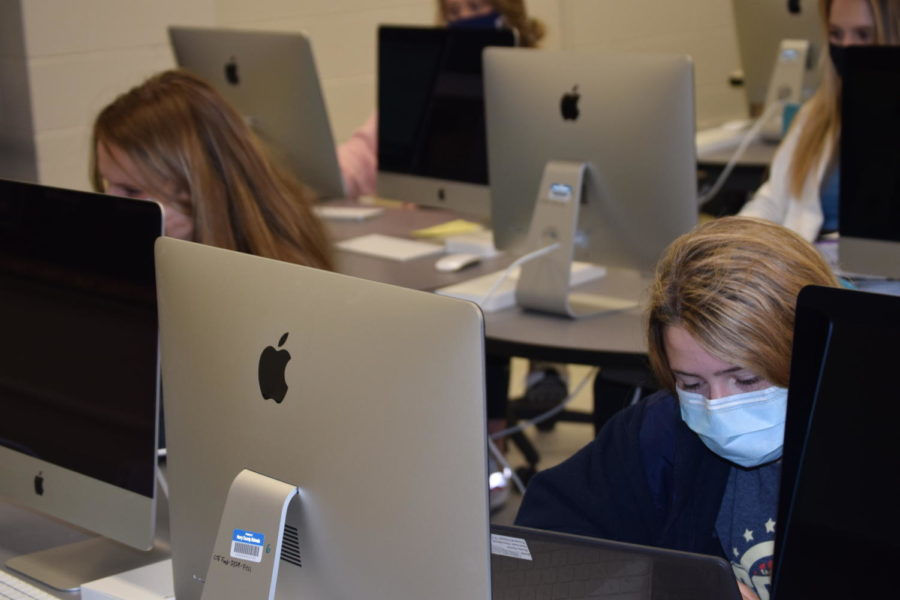 Junior Fianna Steves sits next to a classmate in the Mac lab