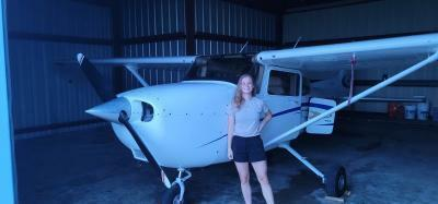 Amber Nophsker stands next to the C 172S plane she learned how to fly this summer.