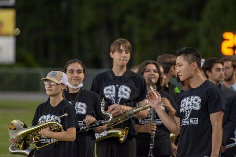 Mr. Jung gives band students a pep talk at a football game.
