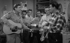 A scene from Episode 19, Season 1, of The Andy Griffith Show, Andy suspects that Barney and a few other citizens have been taken in by a slick music-recording man from out of town.